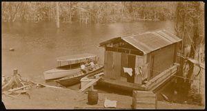 """Euphemia"" motor boat, next to a piragua and a motor boat(?). Also, a boat storage(?) floating shed. Possible location Gatun Lake or Chagres River. | Bote a motor ""Euphemia"", junto a una piragua y bote a motor(?).  Además depósito flotante para guardar botes(?). Posiblemente en Lago Gatún o Río Chagres."